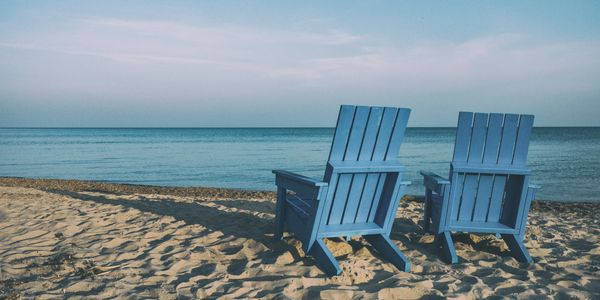 two blue chairs on beach facing water