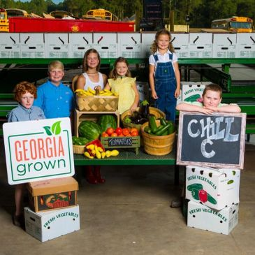 Children standing with fresh vegetables. Georgia Grown sign and Chill C Farms sign.