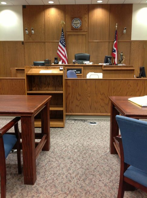 Image of a courtroom, including a judge's bench and attorney tables.