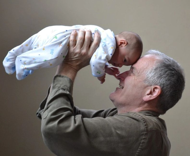 Image of an older gentleman holding a baby so that their foreheads touch.