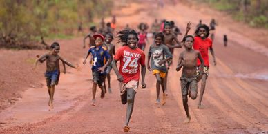 Photograph of Aboriginal kids running on a dirt road Elcho Island NT by Wayne Quilliam