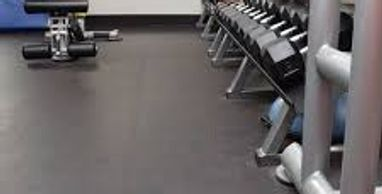 Rubber flooring installed wall to wall in apartment complex home gym with weight lifting bench and dozens of dumbells,