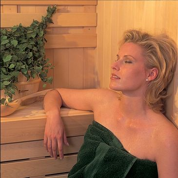 Woman sitting and relaxing in a cedar sauna.