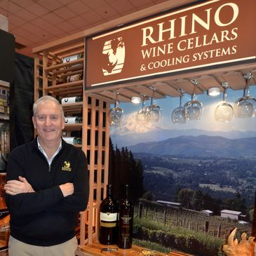 Doug M Smith, the owner of Rhino Wine Cellars, standing in front of a wood wine rack display.