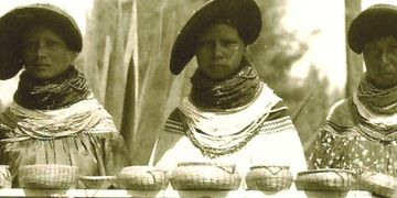 Seminole women displaying pine needle and swamp grass baskets.