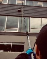 Owner window washing using a water fed pole in Dartmouth,