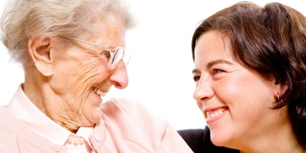 Elder and carer smiling at each other