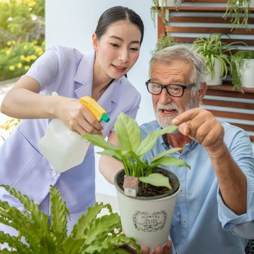 Carer helping elder with watering the plant