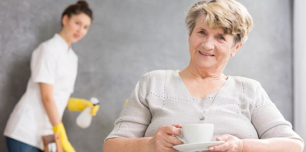 Carer helping elder with cleaning