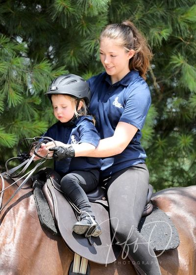 young rider with her riding instructor