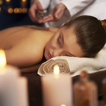 Lady relaxing having a massage with candles around her