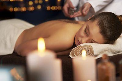 Lady relaxing with Swedish massage with candles around.