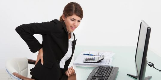 Business woman working at desk with back pain