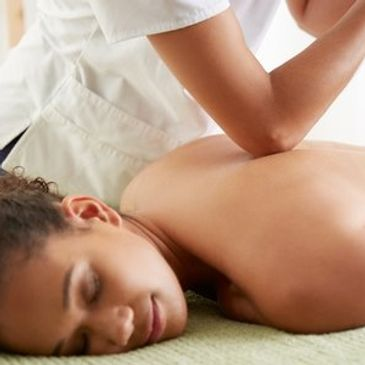 Lady with back and neck pain having deep tissue massage