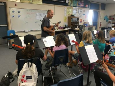 Male teacher in a music classroom, directing several elementary students playing ukuleles