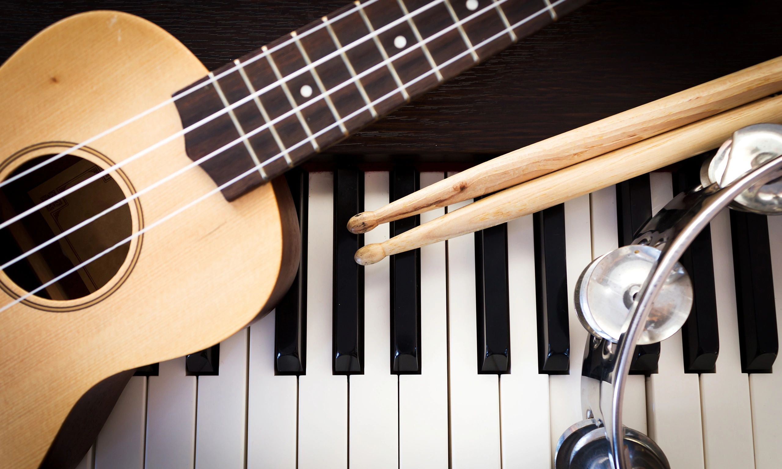 Ukulele, drum sticks, tambourine, and piano keyboard