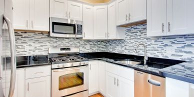 completed kitchen with new granite countertops and fancy backsplash