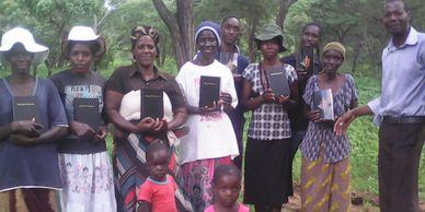 Pastor Knowledge with believers receiving new bibles.