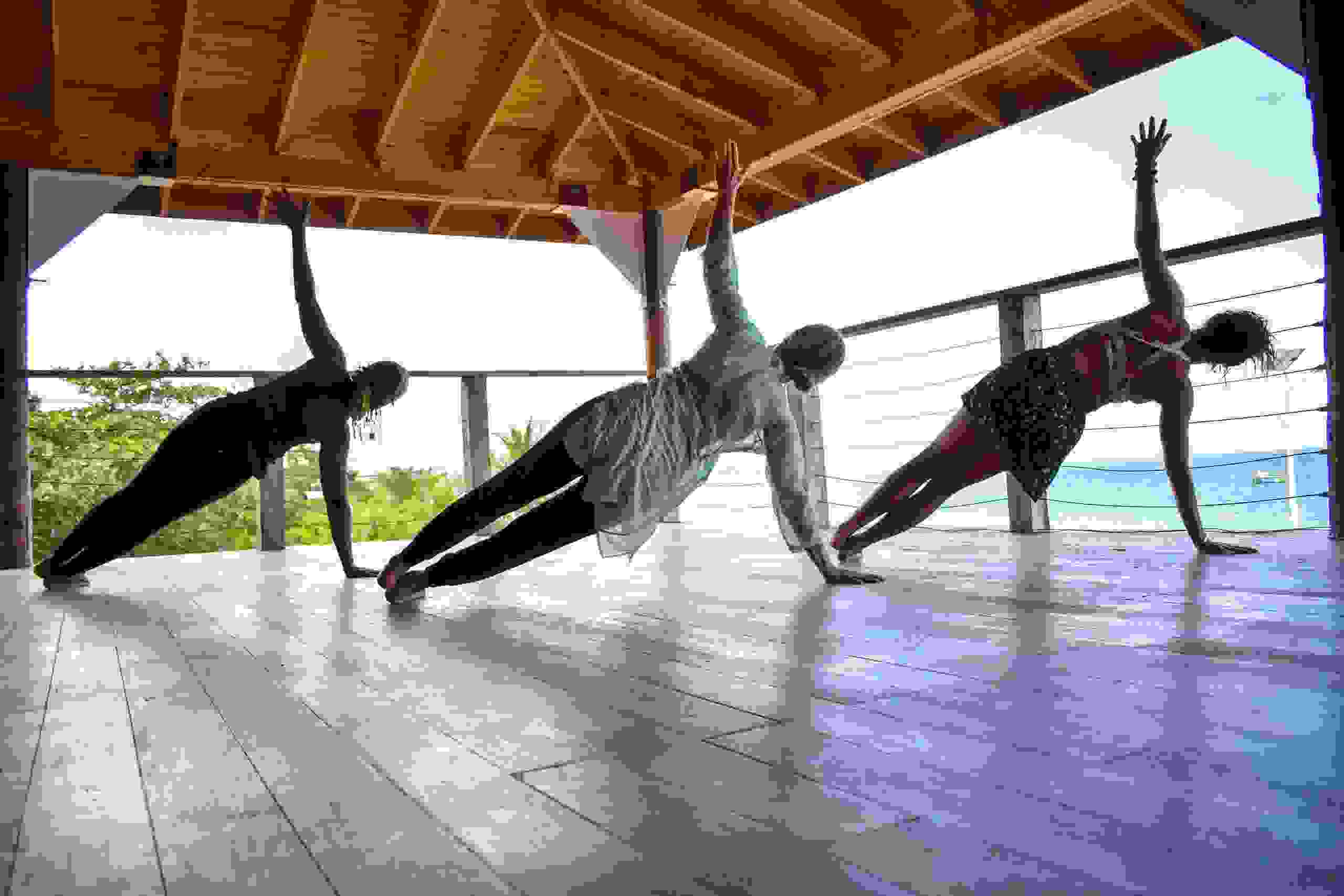 Fanette leads her students in side plank in her hatha iyengar yoga class in Negril, Jamaica.