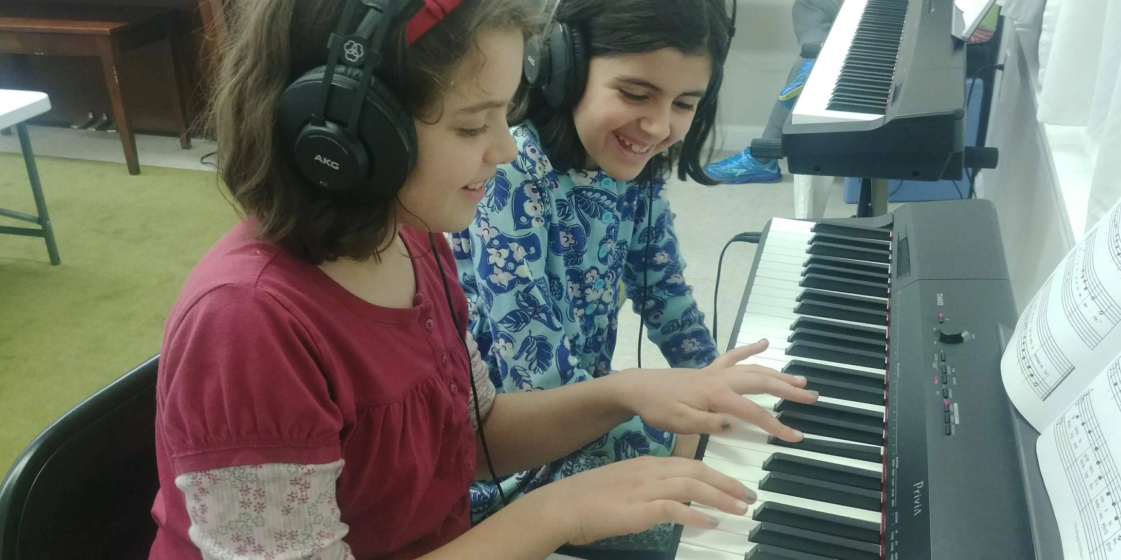 Two smiling girls playing piano together on headphones