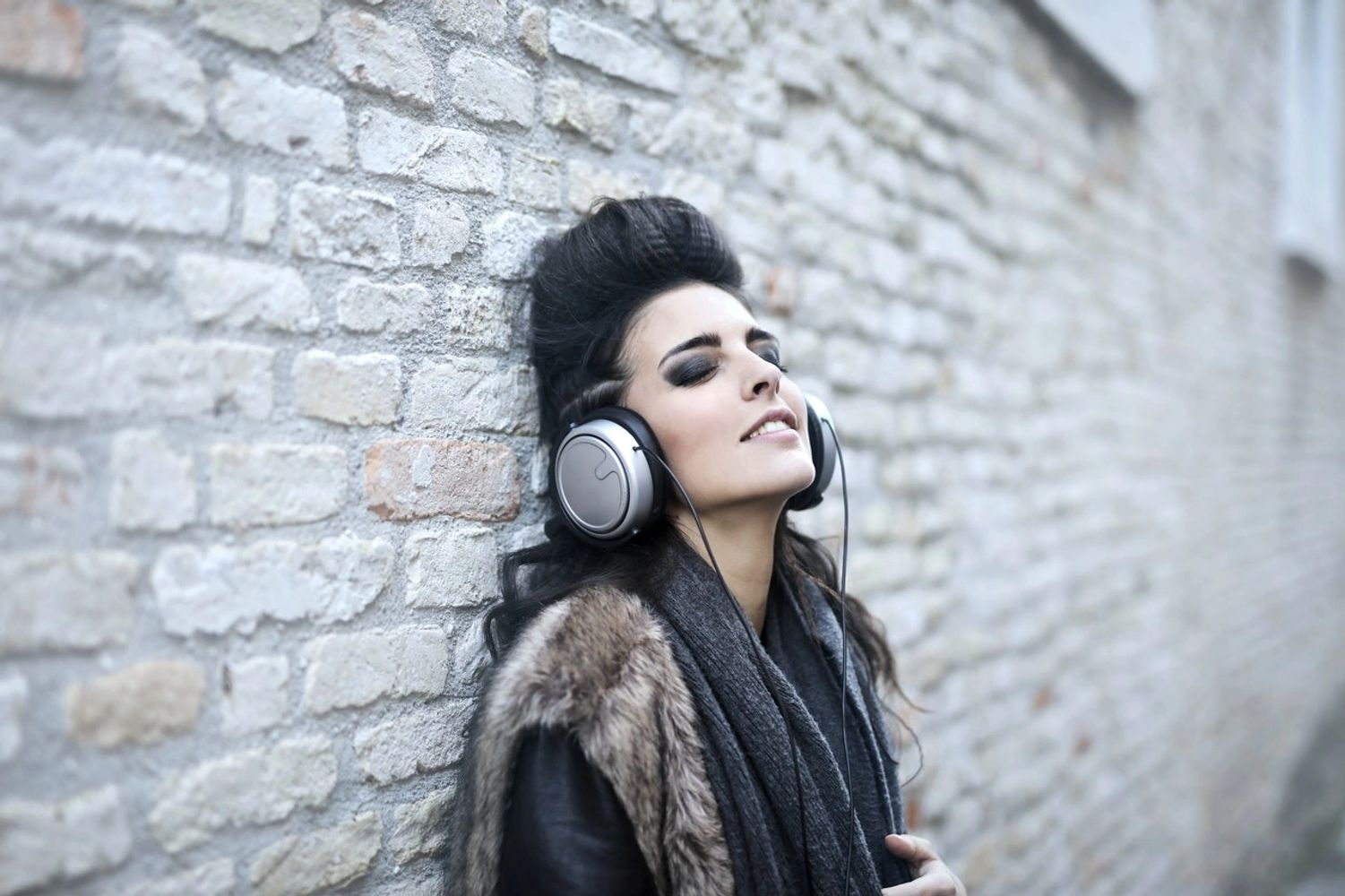 Girl wearing headphones listening to music and leaning on wall.