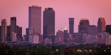 New Orleans skyline against a pink sunset.