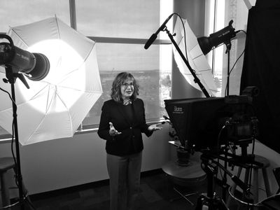 Anne Libby talking to camera, black and white photo