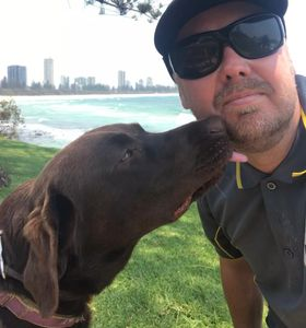 Owner of Happy Dog Training being licked on the face by Brown Labrador at park, ocean background