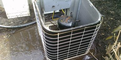 AC condenser sitting in muddy water