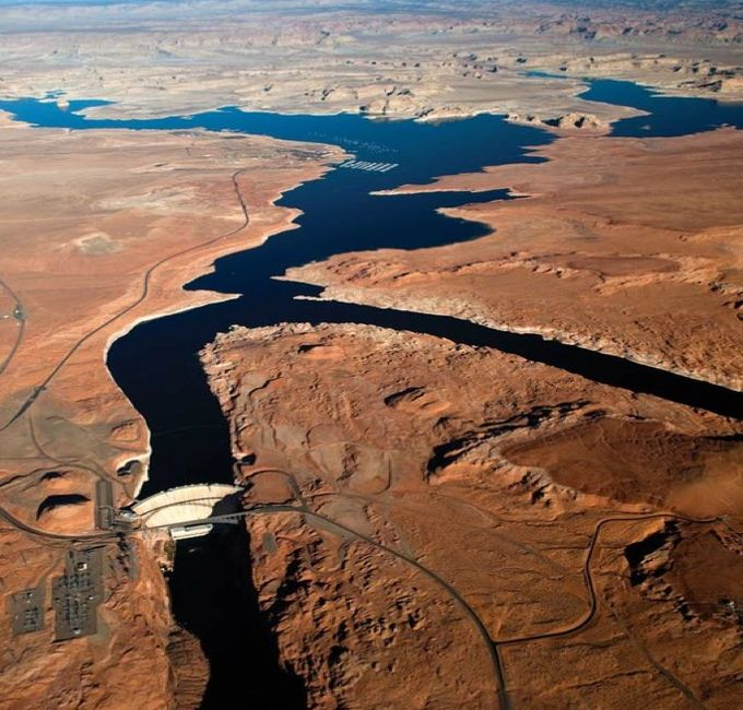 Glen Canyon Dam and Lake Powell, with the Cummins Plateau rising in the distance.