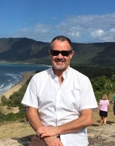 Kim Agnew white man with short grey hair, sunglasses and grey facial hair in front of a beach and mo