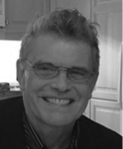 Black and white photo of smiling Caucasian man with short hair and glasses.
