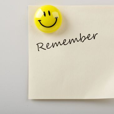Post-it note reads 'remember' and is held to wall/fridge by a magnet in shape of a smiley
