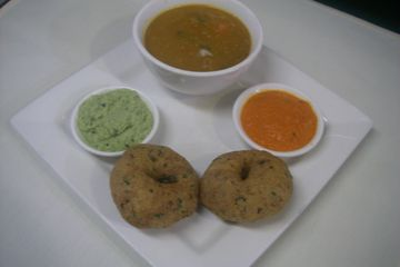two fried lentil donuts served with samber and chutneys