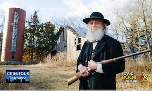 Kerry Altenbernd as John Brown standing in front of barn at Black Jack Battlefield and Nature Park