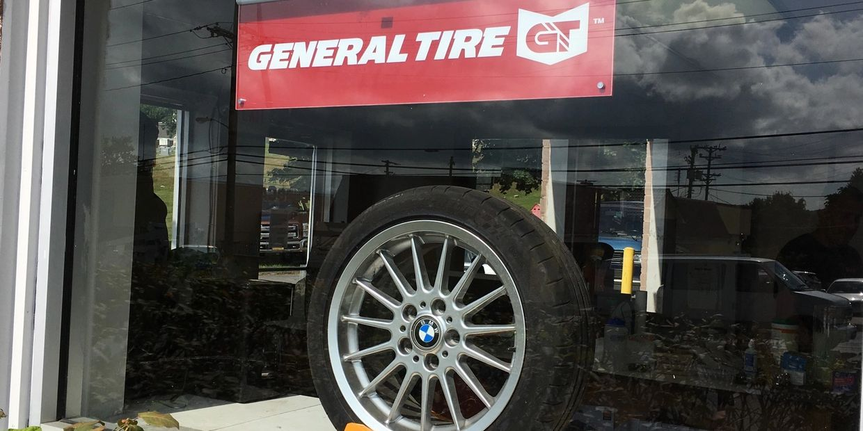 General tire mounted on wheel and logo banner together displaying in store front window