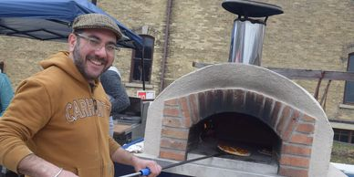 Pizza chef cooking wood-fired pizza in outdoor oven