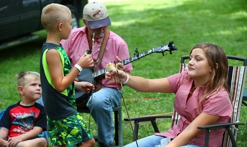 Banjo picking dad with family enjoying s'mores at the Backbone Bluegrass Festival.