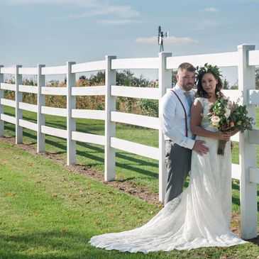 Bride and Groom along white fence in meadow at Alum Creek Farm Wedding Venue