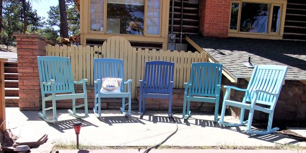 Five blue rocking chairs on sunny patio waiting for you!