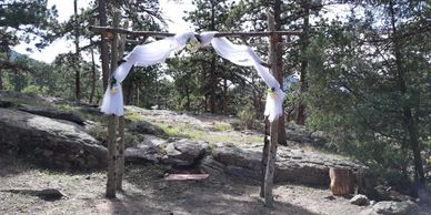 Rustic wood wedding arbor surrounded by evergreen trees.