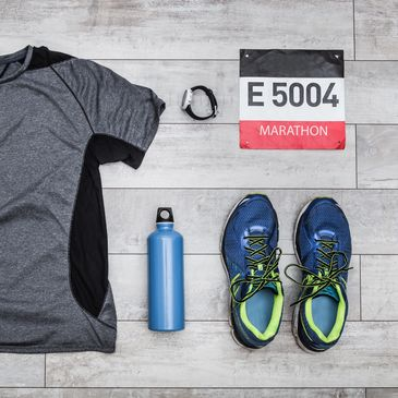 Running flat lay with a watch, bib number, trainers and water bottle.