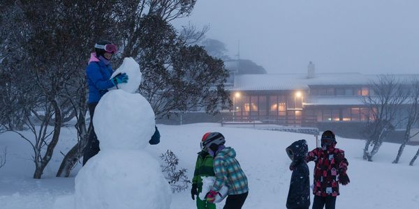 Kids building snowman outside Valhalla Perisher Family Accommodation