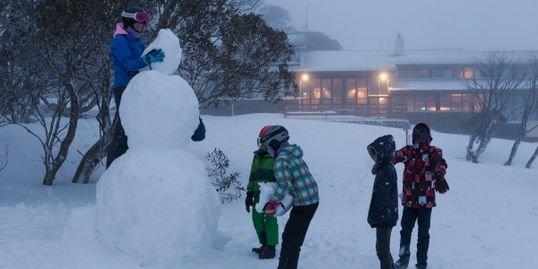Kids building snowman outside Valhalla Lodge Perisher