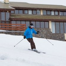 Skier skiing out of Valhalla Lodge Perisher