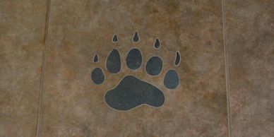 Waterjet cut tile inlay of a custom grizzly paw print for a home restoration in 2011.