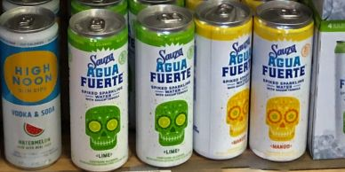 row of cans of sauza agua fuerte in flavors like lime and lemon. shelf of seasonal alcohol drinks