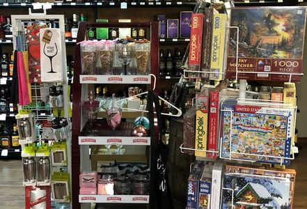 gift shelf in liquor store of puzzles, aprons, cups and glasses, coasters, cards. variety of gifts