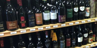 liquor store shelf of wines.white wine and red wine. cabernet merlo chardonnay, pino noir and blends
