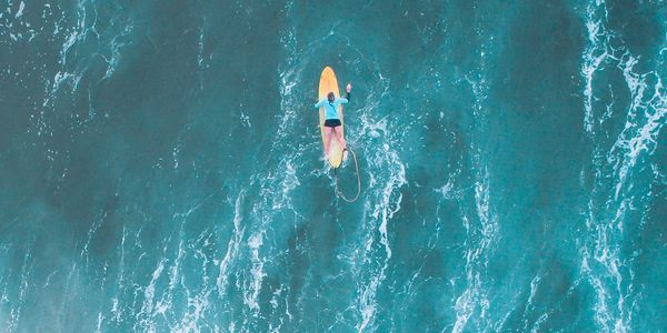 Sea inspired drone image of surfer girl in the waves near Coffs Harbour